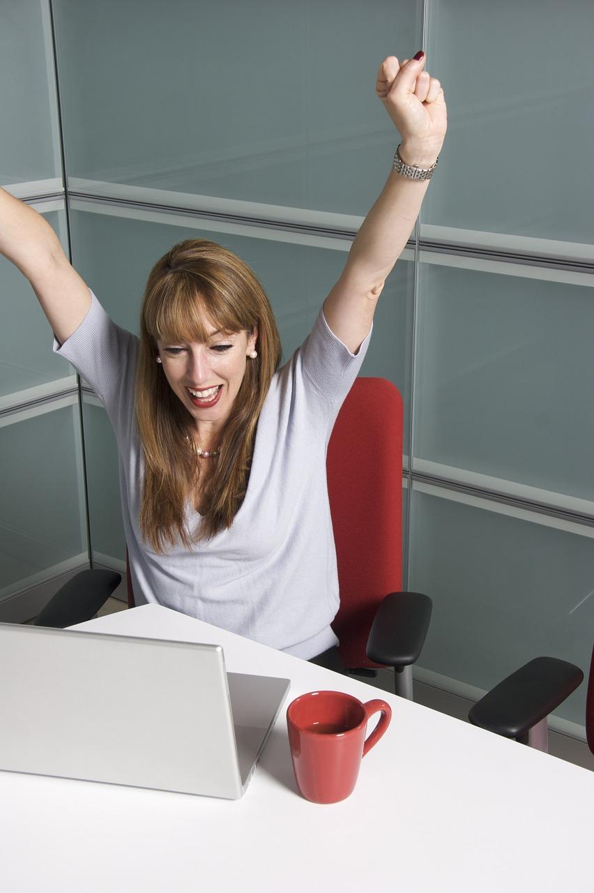 woman cheering at desk