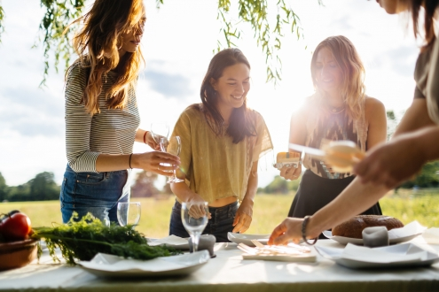 Three young women preparing and decorating a table outside in a huge garden for a dinner party